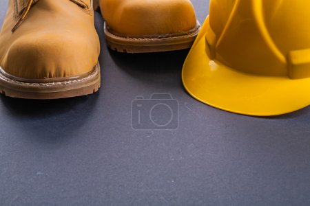 Working boots and yellow helmet