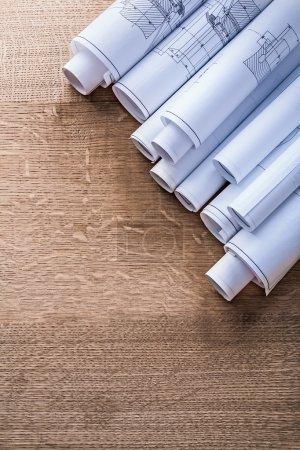 Rolls of blueprints on wooden board