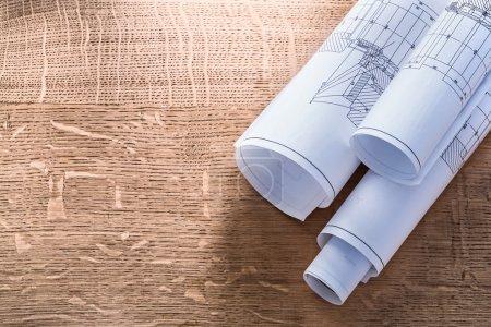 Rolls of blueprints on wooden board