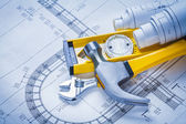 Construction level, claw hammer, blueprints