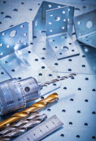 Metal ruler, power drill, bits