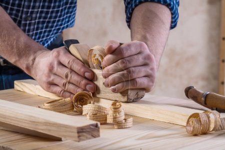 Joiners hands with woodworkers plane