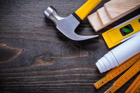 Photo pour Niveau de construction, plan enroulé, marteau à griffe, compteur en bois et briques sur fond de surface en bois vintage - image libre de droit