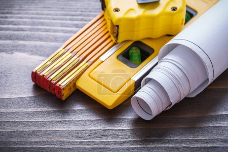 Tape-measure, blueprints and construction level