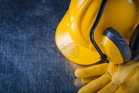 Photo pour Casque, protège-oreilles et gants de protection en cuir rayé métallique surface, concept de construction. - image libre de droit