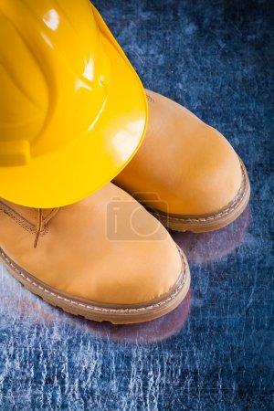 Photo pour Bottes de travail de sécurité et casque dur sur fond métallique rayé, concept de construction . - image libre de droit