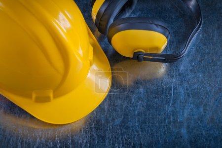 Photo pour Manchons jaunes d'oreille de sécurité et casque de travail sur le fond métallique rayé, concept de construction. - image libre de droit