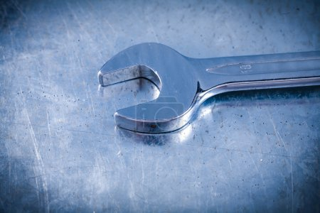 Photo for Stainless spanner wrench on scratched metallic background, top view, construction concept. - Royalty Free Image