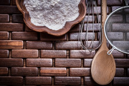 Photo for Composition of wooden spoon, bowl, flour, sieve and egg-whisk. - Royalty Free Image