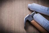 Blueprint rolls claw hammer on wood