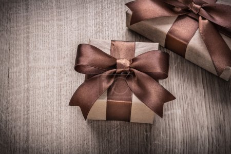 Present boxes with brown bows on wood