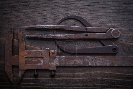 Photo for Rough calipers on vintage wood background construction concept. - Royalty Free Image