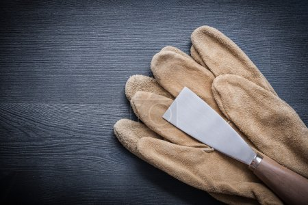 Paint scraper and protective gloves