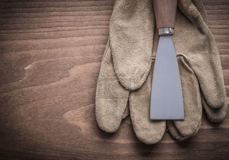 Photo for Paint scraper on safety gloves on wooden background. - Royalty Free Image