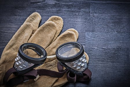 Photo for Close-up of goggles on gloves on wooden table - Royalty Free Image