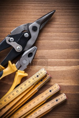 Photo for Composition of tin snips, pliers and wooden meter construction concept - Royalty Free Image