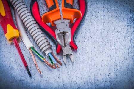 Photo for Nippers and insulated screwdriver corrugated pipe wire protection on metallic background - Royalty Free Image