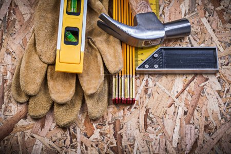 Photo for Claw hammer, leather gloves, construction level, wooden meter, square ruler. - Royalty Free Image