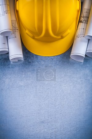 Blueprint rolls and yellow building helmet
