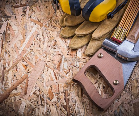 Photo for Safety gloves, wooden meter, handsaw, claw hammer, earmuffs on OSB - Royalty Free Image
