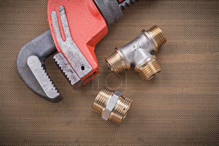 Plumbers wrench and brass plumbing fixtures