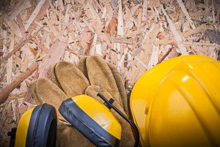 Photo pour Gants de cuir sécurité, bâtiment casque, casque anti-bruit sur aggloméré. - image libre de droit