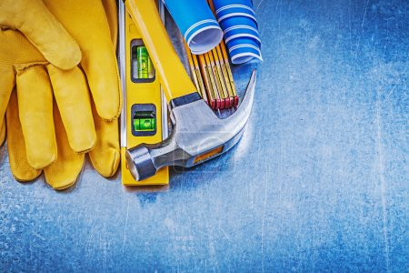 Safety gloves, hammer and construction level