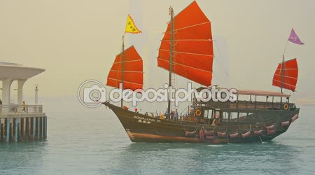 Tour boat. patterned after an old fashioned Chinese sailing junk. approaching a dock in Victoria Harbor. Hong Kong.