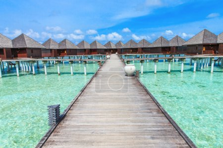 Beach with bridge to water bungalows
