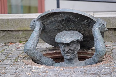 Statue of man getting out of a manhole