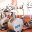 Elliptical cross trainer in a row in a gym...