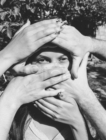 Photo pour Modèle féminin avec plusieurs mains sur son visage en noir et blanc. - image libre de droit
