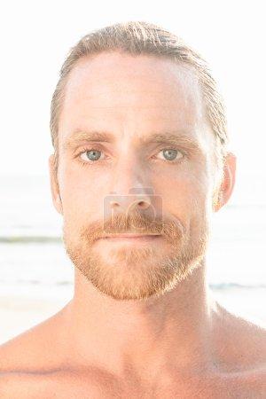 Photo pour Bel homme blond aux épaules nues et une barbe regardant directement la caméra sur un fond de plage avec éclat du soleil d'été - image libre de droit