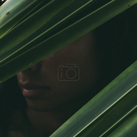 Woman concealed behind palm fronds