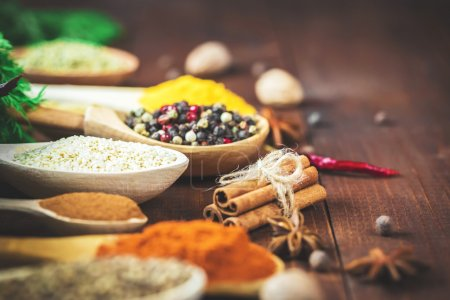 Photo for Beautiful colorful spices in wooden spoons and bowls on an old wooden brown table. - Royalty Free Image