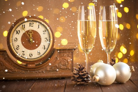 Glasses of champagne and ancient clock