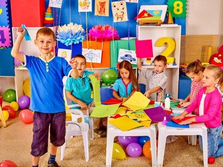 Group kids holding origami airplane in kindergarten .