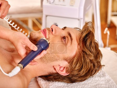 Young man receiving electric facial massage.