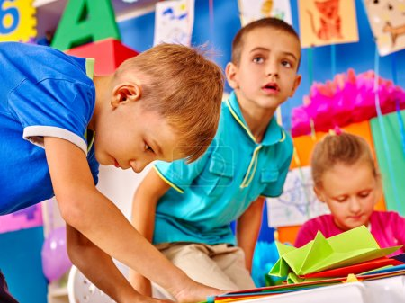 Group kids learn do origami airplane in kindergarten .