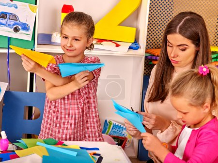 Photo for Woman with little girls playing origami paper airplane in kindergarten preschool. - Royalty Free Image