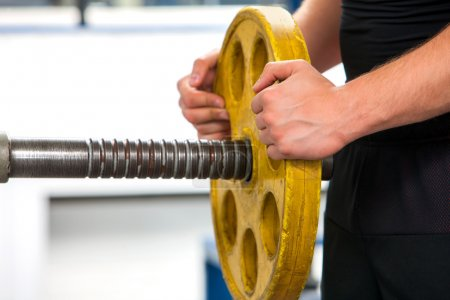 Photo for Close up of male hands lifting yellow heavy barbell at gym. - Royalty Free Image