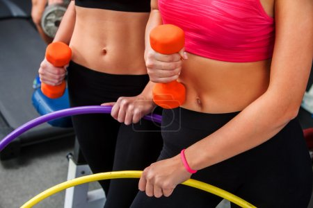 Bare female belly  with dumbbells and hoop  at gym.