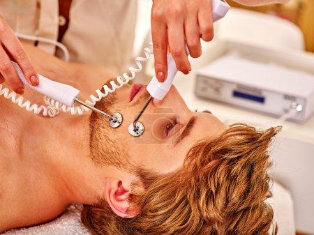 Man receiving electric facial peeling hydradermie massage.