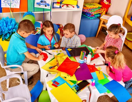 Photo for Group kids holding colored paper on table in kindergarten. Children use a colored origami paper. - Royalty Free Image
