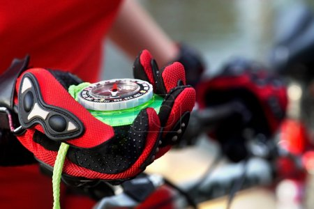 Female hands wearing bicycle gloves keeps compass.