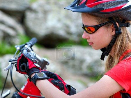 Photo pour Vélo fille cycliste. Montre de fille de cycliste sur la montre intelligente. Fille recherchant la route. Smart watch meilleur assistant en Voyage. Pierres sur le fond. - image libre de droit