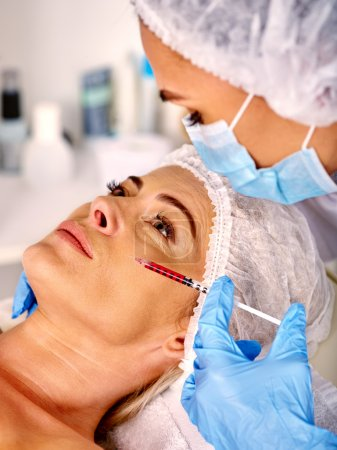 Woman middle-aged in spa salon giving botox injections.
