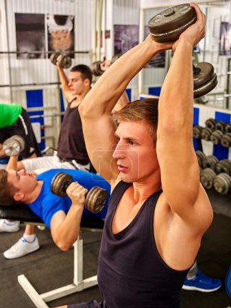 Photo for Group of men working on simulator his body at gym. Strong man with dumbbells on foreground into gym. - Royalty Free Image
