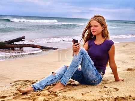 Girl on sand near sea call help by phone.