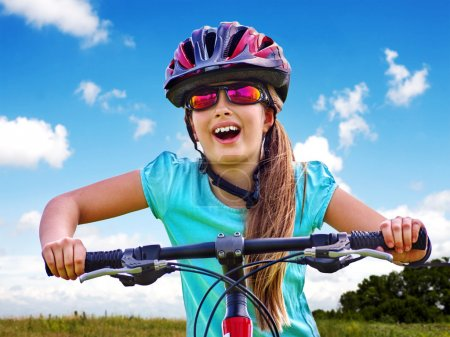 Photo for Bikes bicycling child. Girl rides bicycle. Girl wearing sport colored sunglasses. Cyclist look up. - Royalty Free Image